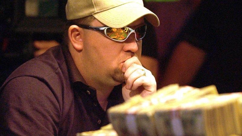 Крис в очках, кепке и прикрывает рот рукой